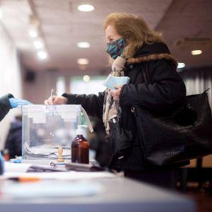 Una votante deposita su papeleta en el colegio electoral constituido en la Residencia Universitaria Campus La Salle, en Barcelona