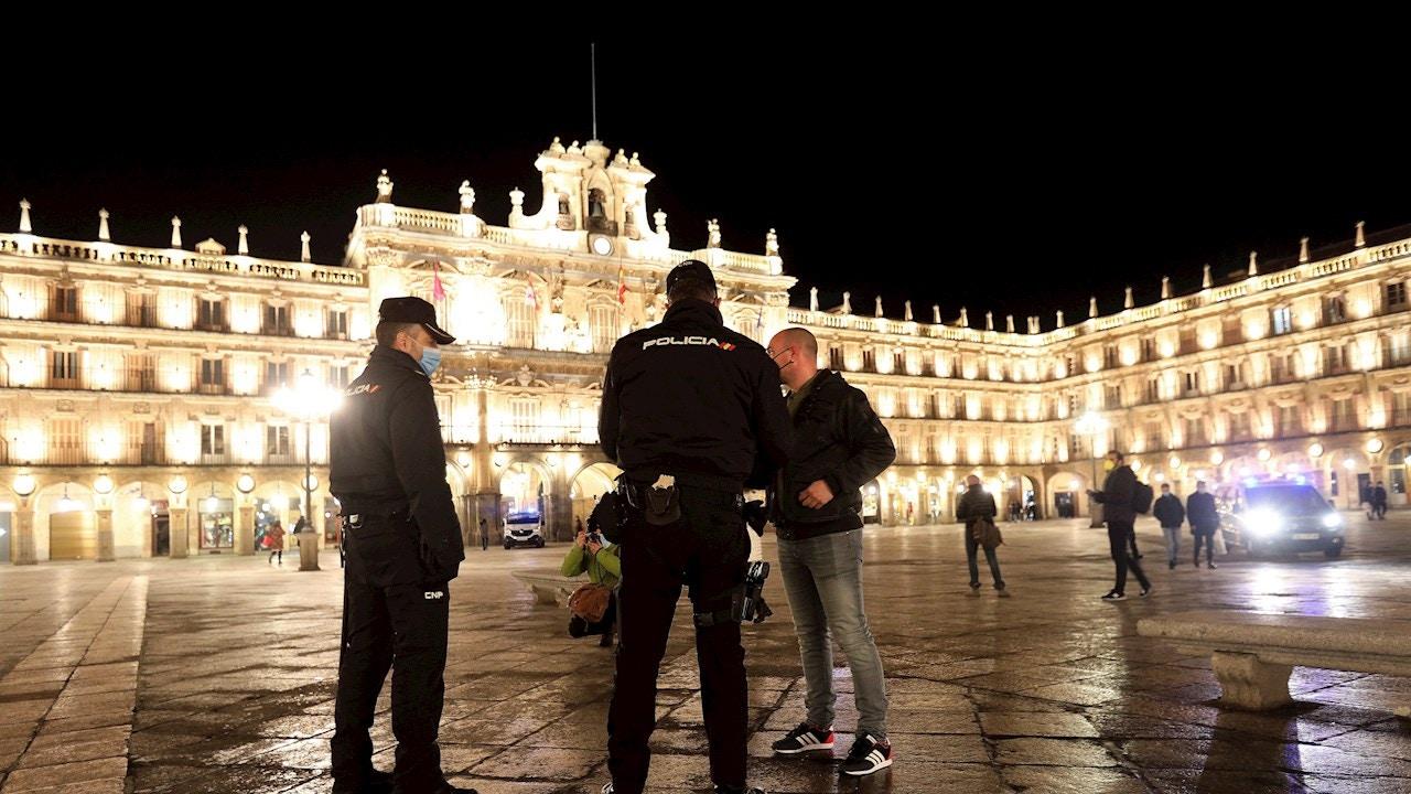 Dos agentes de la Policía Local y Nacional hablan con un ciudadano en la Plaza Mayor de Salamanca