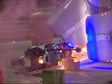 Los manifestantes tiran a un policía y queman su moto en las protestas en Lleida por la detención de Pablo Hasél
