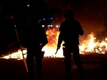 Agentes de los Mossos junto a una barricada en llamas en la Calle Aragó