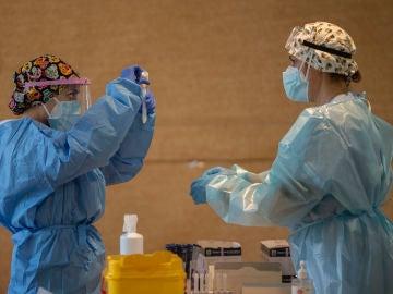 Un trabajador sanitario sostiene una probeta en un dispositivo de cribado masivo de antígenos en Alcorcón