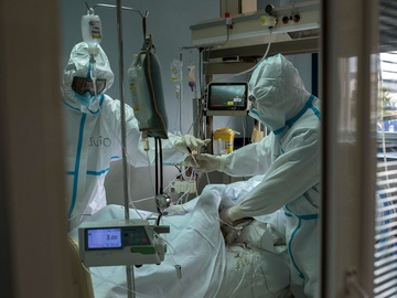 Trabajadores sanitarios atienden a un paciente con coronavirus en la UCI