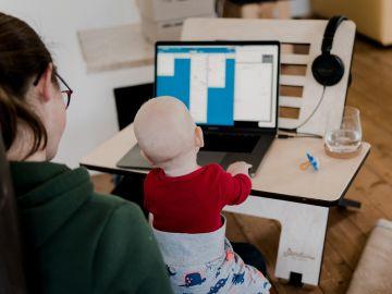 Imagen de archivo de una madre teletrabajando con su bebé