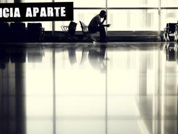 Un hombre espera en un aeropuerto
