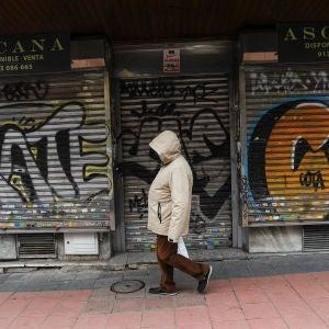 Una persona pasea delante de un local cerrado en Madrid