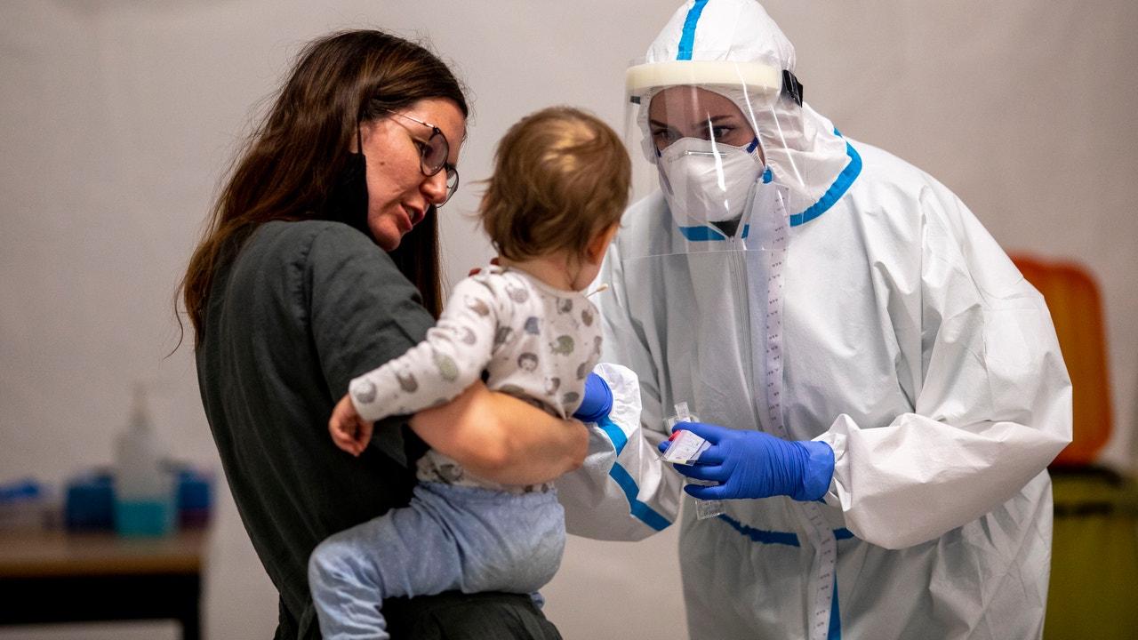 Un sanitario testea a una madre y un hijo en Berlín.