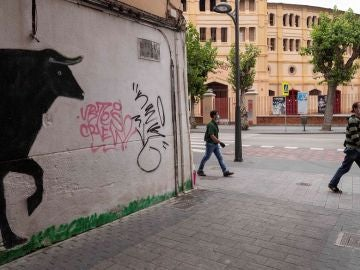 Dos hombres caminan junto a la plaza de toros de la Condomina de Murcia