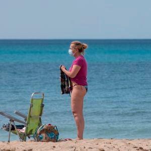 Una mujer utiliza la mascarilla en la playa