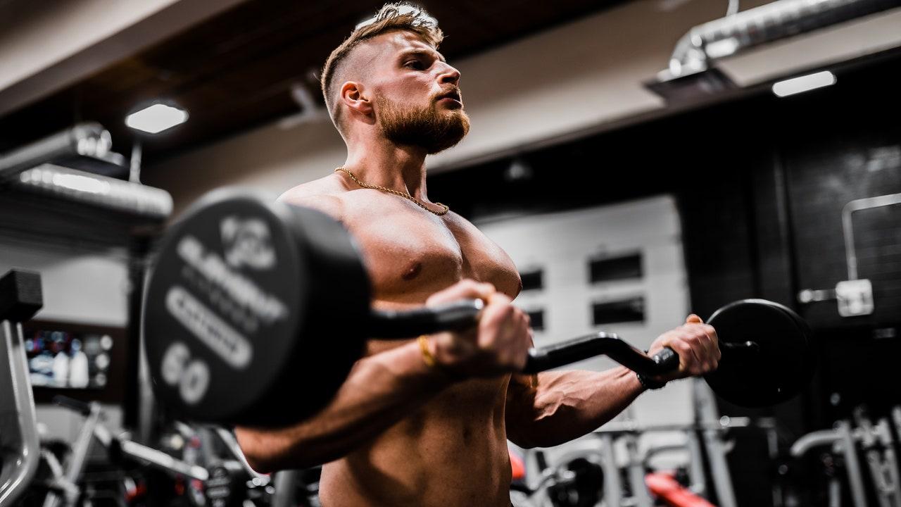 Un hombre entrena en un gimnasio con una barra de pesas