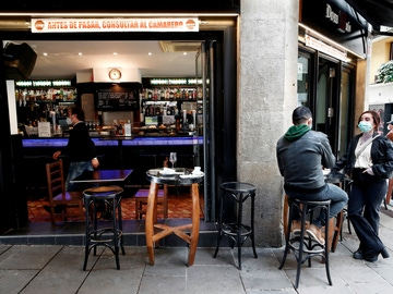 Dos personas toman un aperitivo en el exterior de un bar de Pamplona