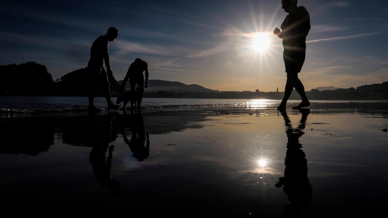 Varias personas se bañan este jueves al amanecer en la playa de Ondarreta de San Sebastián.