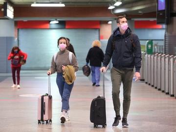 Imagen de archivo de personas con maletas en una estación de tren