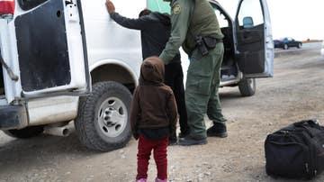 Un niño observa cómo un agente de la Patrulla Fronteriza de los EE. UU. registra a un compañero inmigrante centroamericano en 2019