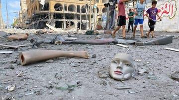 Partes de un maniquí roto yacen este miércoles en el suelo cerca de una torre que fue alcanzada por ataques aéreos israelíes en Gaza