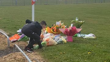 Niño depositando flores en el lugar donde falleció Jordan Banks